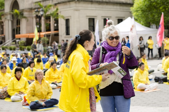 A Falun Dafa practitioner distributes origami lotus flowers to passerby.  (Samira Bouaou/The Epoch Times)