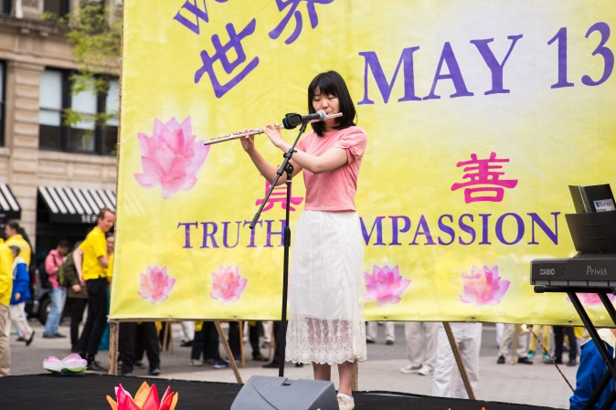 A woman plays the flute during the World Falun Dafa Day event at Union Square, New York City, on May 11, 2017. (Benjamin Chasteen/The Epoch Times)
