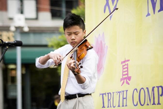 Yuan Yuan, a young violin soloist performs during the World Falun Dafa Day event at Union Square, New York City, on May 11, 2017. (Samira Bouaou/The Epoch Times)