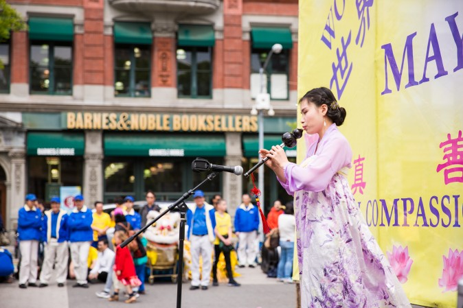 Yue Dai plays the hulusi, an ethnic instrument made of gourd and bamboo, during the World Falun Dafa Day event at Union Square, New York City, on May 11, 2017. (Benjamin Chasteen/The Epoch Times)