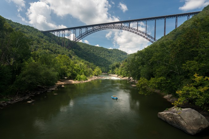 Rafters float towards the rapids under the high arched New River Gorge bridge in Victor, W.Va. (Steve Heap/Shutterstock)