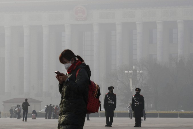 A woman wears a mask for protection against the air pollution on Tiananmen Square in Beijing as the city is blanketed by heavy smog on Jan. 4, 2017. (AP Photo/Andy Wong)