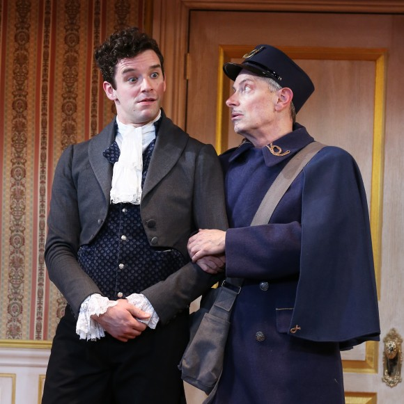 (L–R) Ivan Alexandreyevich Hlestekov (Michael Urie) who is assumed to be government official sent to spy on the town, and the Postmaster (Arnie Burton), in