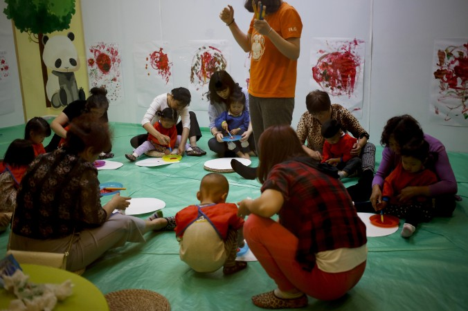 In this Wednesday, May 11, 2016 photo, children accompanied by their parents and caretakers, attend an art class at the I Love Gym center in Beijing. A television personality in China argues that children are taught to lie from a young age. (AP Photo/Andy Wong)