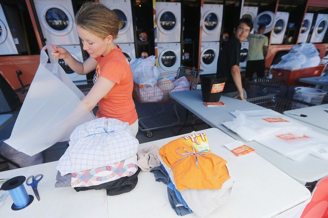 Worker Holly Rochelle sorts a resident's laundry washed for free at the Tide Loads of Hope mobile laundromat set up for those affected by Hurricane Isaac in LaPlace, Louisiana on Sept. 6, 2012. (Mario Tama/Getty Images)