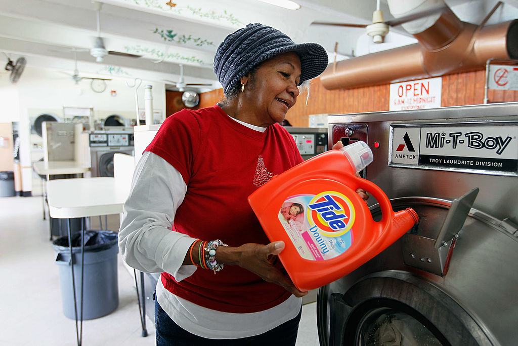 Nicole Alcaraz pours Tide laundry detergent into a laundry machine in Miami, Florida on March 13, 2012. (Joe Raedle/Getty Images)