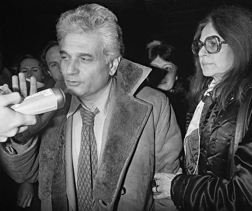 French philosopher Jacques Derrida and his wife, Madeleine, respond to questions from reporters at la Gare de l'Est in Paris on Jan. 2, 1982. (JOEL ROBINE/AFP/Getty Images)