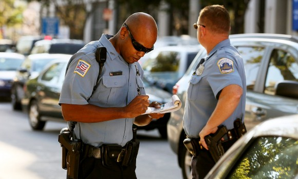 Metropolitan Police Officer Tyrone Gross (L) writes a ticket to a motorist on September 21, 2010 in Washington, DC. (Mark Wilson/Getty Images)