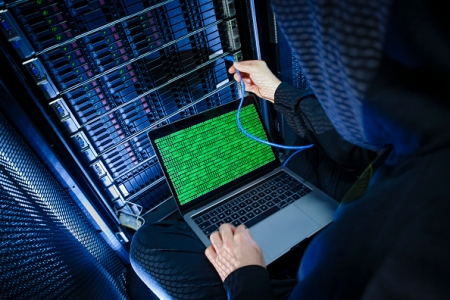 Symbolic photo with topic online crime, data theft and piracy: A man poses with a laptop showing a binary code in front of Server racks in a server center on January 12, 2018, in Berlin, Germany. (Thomas Trutschel/Photothek via Getty Images)